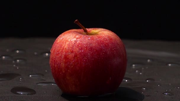 Drop fresh water on a red apple on black background in Slow Motion