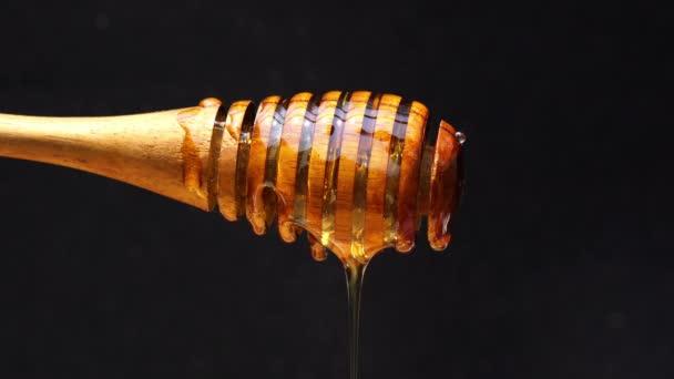 Med, který stéká z medové naběračka na tmavém pozadí
