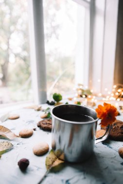 Cup with tea near the window with autumn leaves and cookies