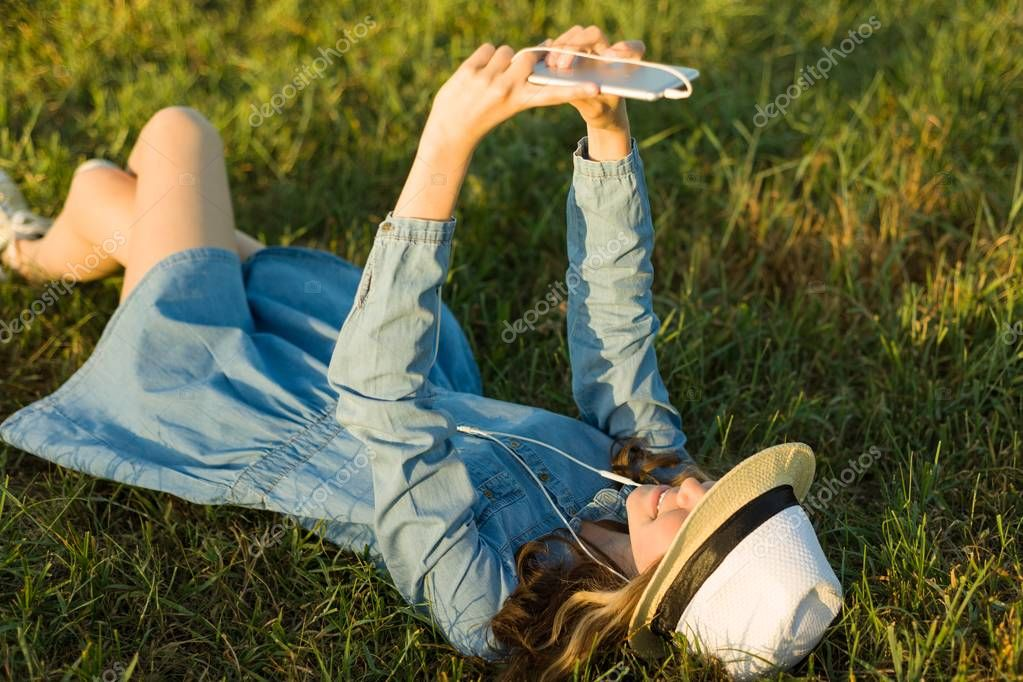 Portrait of teenage girl 14 years old lying on the grass. Girl in dress hat, in her headphones holds a smartphone, listens to music makes a selfi photo.View from above