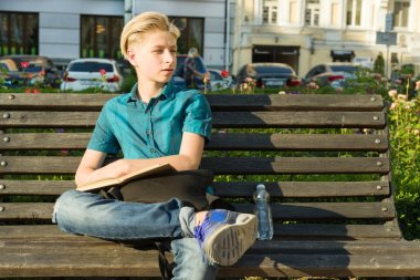 Outdoor portrait of teenage boy of 13, 14 years old sitting on bench in city park