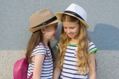 Outdoor summer portrait of two happy girl friends 7, 8 years in the profile of talking and laughing. Girls in striped dresses, hats with backpack, background gray wall