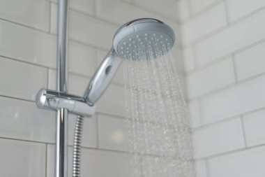Close-up of chrome shower, faucet, in the bathroom covered decorative ceramic tiles with white glossy bricks. Water running from shower head.