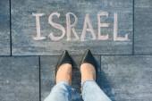 Blick von oben, weibliche Füße mit Text Israel geschrieben am grauen Bürgersteig