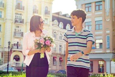 School student congratulates his teacher with bouquet of flowers. Teacher's Day