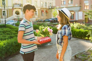 Teenager boy congratulates girl with bouquet of flowers and gift outdoors. Friendship and people concept