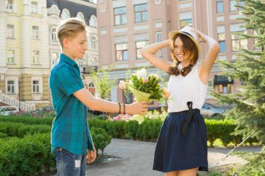 Teenager boy congratulates the girl with bouquet of flowers outdoors. Friendship and people concept