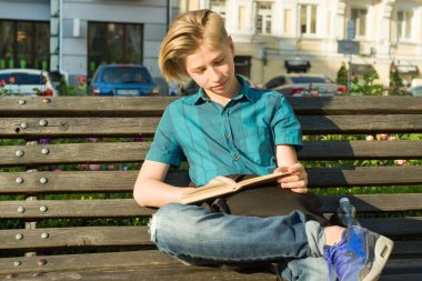Outdoor portrait of a teenage boy and girl 14, 15 years old, sitting on bench in city park with book