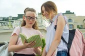 Photo Portrait of two schoolgirls of teenagers with school backpacks and books.