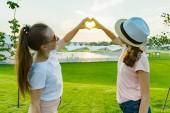 Fotografie Přátelství dvou dospívajících dívek, nejlepší přítelkyně bavit v přírodě, na zeleném trávníku rekreační park a zábavní, Ukázat rukou na srdce na slunce pozadí v parku