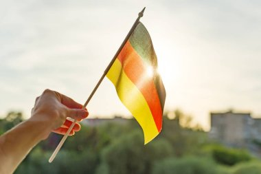 Hand holding Germany flag an open window. Background blue sky, silhouette of the city, sunset