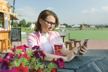 Mature woman resting sitting at table in summer street cafe, looking at mobile phone, smiling. Background green zone of the park rest and entertainment