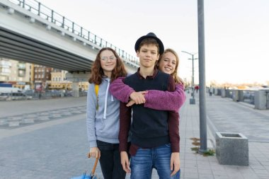 Outdoor city portrait of three friends teen boys and girls 13, 14 years old