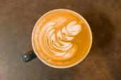 Pohled shora, latte art, šálek kávy na šedé kamenné desky stolu