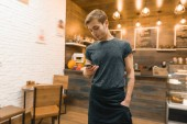 Junger Mann in Kittelschürze Coffeeshop-Mitarbeiterin am Tresen, bestellt per Smartphone