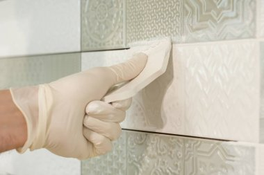 Closeup of tiler hand rubbing tile, Installing and grouting decorative finishes in environments with an high aesthetic value. Two-component, decorative, acid resistant epoxy grout