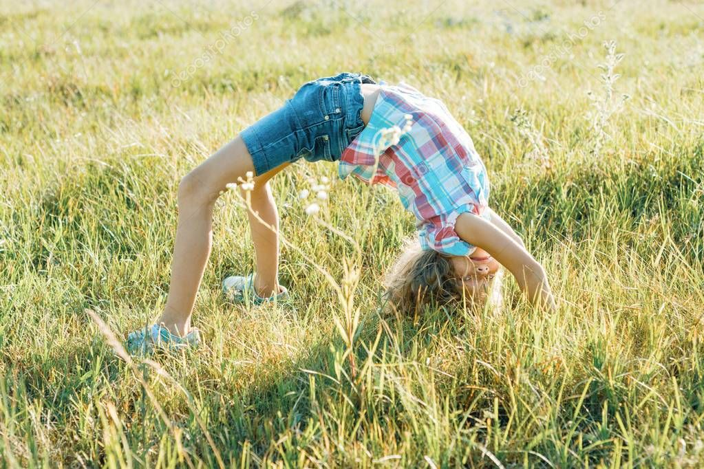 Happy little athletic girl child doing an acrobatic handstand on nature in summer park