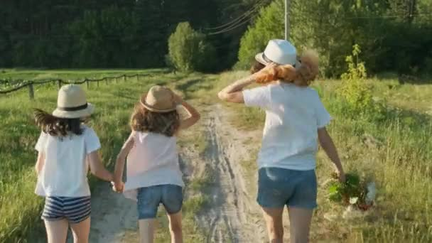 Děti tři dívky v kloboucích drží ruce v běhu na venkovskou silnici