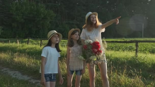 Three girls children with bouquet of flowers show finger on the road, emotions joy and happiness, wait and meet