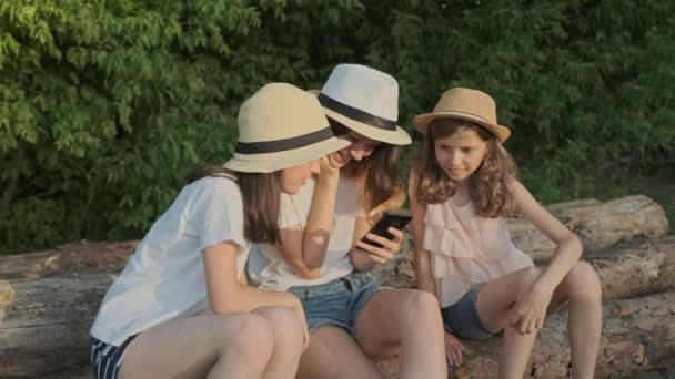 Group of children, three girls sitting on logs in nature and looking at smartphone