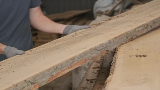 Close-up of carpenters hands with plank wood at carpentry woodworking workshop.