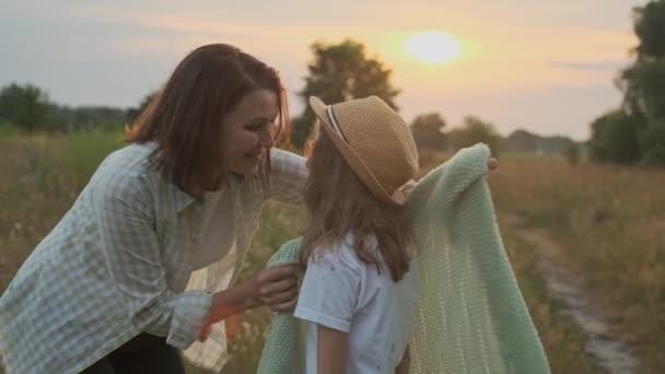 Loving moms puts on daughter knitted blanket