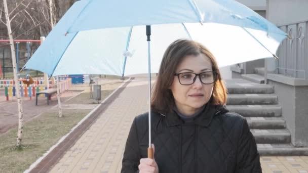 Ältere lächelnde Frau im Mantel mit Brille und Regenschirm, im Freien Frühling Herbst Wintersaison.