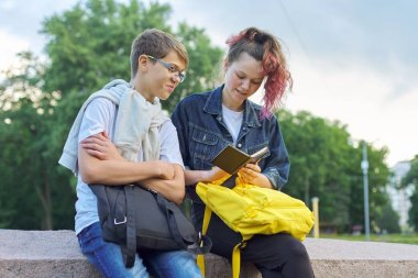 Outdoor portrait of two talking teenagers students