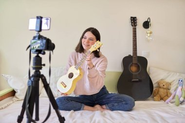 Teenager girl plays music on ukulele, online learning and chatting with followers
