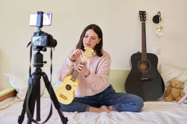Teen girl playing on ukulele. Blog, music channel, vlog,