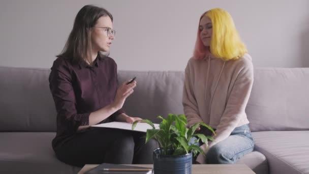 Teen girl giving interview to social worker. Školní psycholog mluví se studentem, poradenství, terapie, pomoc a podpora dospívajících