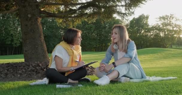 Žena poradce mluvit s mladou ženou student teenager sedí na trávníku v parku na trávě