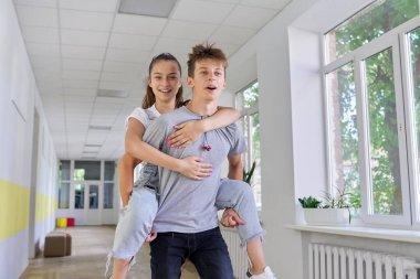 Teenagers boy and girl friends having fun at school