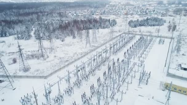Wonderful panoramic view high voltage towers and wire lines at transmission station among snow