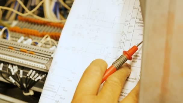 Detailní profesionální elektrikář připojí vodiče pomocí nástroje podle schéma elektrického zapojení v rozvaděči