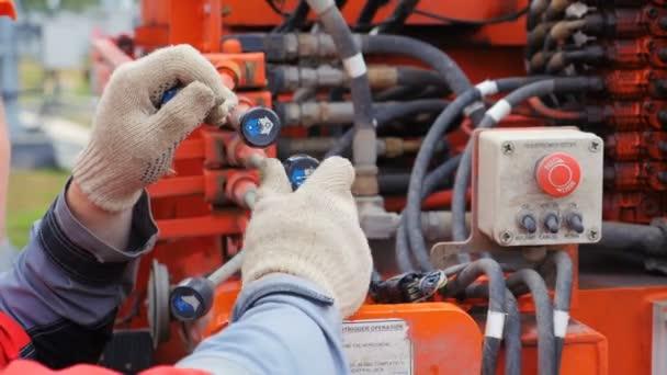 Detailní profesionální elektrikář v uniformě přesune ovládací páky v červené napájecímu zdroji s tlusté dráty