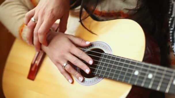 Closeup skilled guy musician teaches young lady to hold guitar and play music with hands and fingers