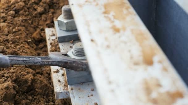 Closeup zkušené zaměstnance řeší spojovacích prostředků na kovové části s nástrojem pro montáž vedení vysokého napětí