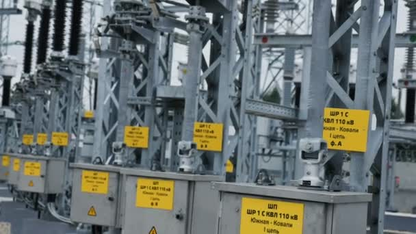 Closeup switchboards with information and danger warning signs under heat-resistant high-voltage insulators at substation