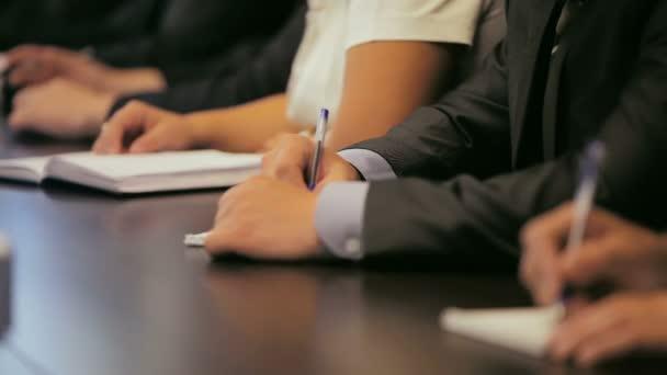 Közelkép az emberek a klasszikus ruhák írja le megjegyzi a papír jegyzetfüzetek office üzleti találkozón