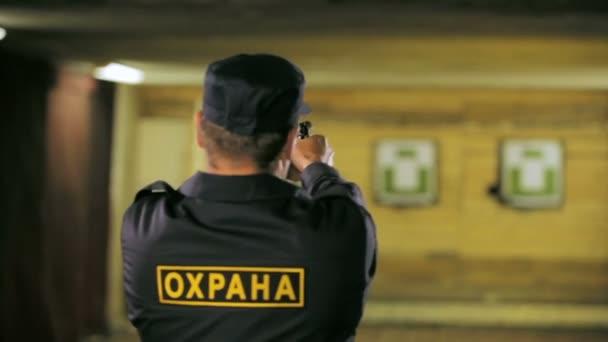 Closeup zadek zobrazit stráž v oblečení se bezpečnostní nápis zlušeností střílet s pistolí v dosahu