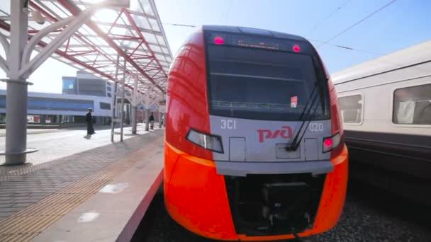 Lidé na palubu moderní vysokorychlostní vlak s logem RŽD cestování na letiště v terminálu nádraží