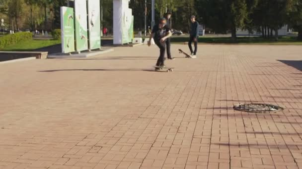 Guy in cap and black t-shirt rides does trick and falls down from skateboard on large city square on sunny day