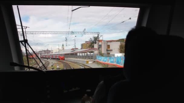 Blick aus der Führerkabine mit Bediener zurück in den Zug, der mit Lokomotive vor blauem Himmel zum Bahnhof einfährt