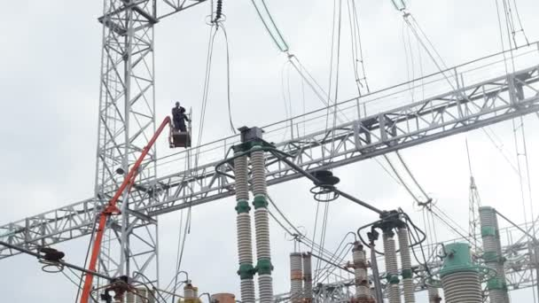 man on crane ground above electric transformers