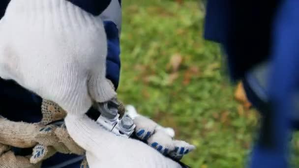 pracovník má kabel a kolega otáčí Nástroj pro upevňovací šrouby