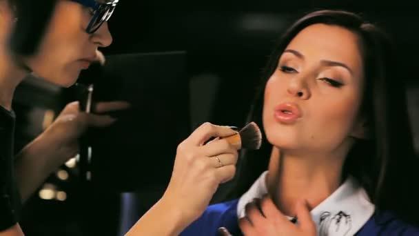 professional makeup artist puts powder on model face