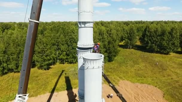 people install tower standing on crane against landscape