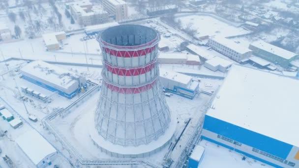Heizstation mit Kühlturm und Schneefall