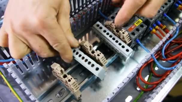Closeup muž elektrikář opraví rukou plastové díly na velkých přenosu rozváděče v dílně